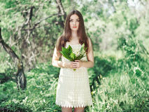 Portrait of beautiful young woman with lily of the valley Stock Photos