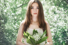 Portrait of beautiful young woman with lily of the valley Royalty Free Stock Image