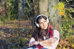 Portrait of beautiful young woman listening music outdoor.Enjoying Music Stock Image