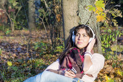 Portrait of beautiful young woman listening music outdoor.Enjoying Music Stock Photos