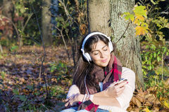 Portrait of beautiful young woman listening music outdoor.Enjoying Music Stock Photo