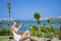 Portrait of beautiful young woman listening music on a sea background Royalty Free Stock Image