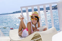 Portrait of beautiful young woman listening music on a sea background. Portrait of beautiful young woman  with straw hat listening music with a tablet.summer Royalty Free Stock Image