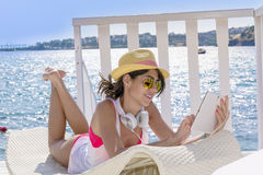 Portrait of beautiful young woman listening music on a sea background Stock Images