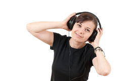 Portrait of a beautiful young woman listening to m. Usic against a white background Royalty Free Stock Photos