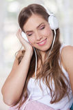 Portrait of a beautiful young woman listening to music with clos Stock Photography
