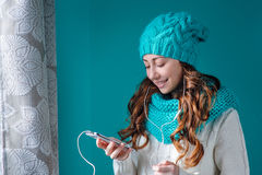 Portrait of a beautiful young woman listening to music on headph Royalty Free Stock Image