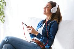 Beautiful young woman listening to music with mobile phone at home. Portrait of beautiful young woman listening to music with mobile phone at home Royalty Free Stock Photography