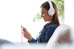 Beautiful young woman listening to music with mobile phone at home. Portrait of beautiful young woman listening to music with mobile phone at home Stock Photography