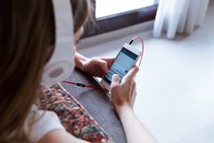 Beautiful young woman listening to music with mobile phone at home. Portrait of beautiful young woman listening to music with mobile phone at home Royalty Free Stock Images