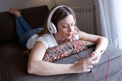 Beautiful young woman listening to music with mobile phone at home. Portrait of beautiful young woman listening to music with mobile phone at home Royalty Free Stock Photo