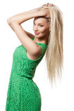 Portrait of girl with long blond hair. Portrait of a beautiful young woman with long blond hair in green dress, isolated on white Stock Photo