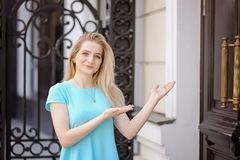 Portrait of beautiful young woman with blond hair and long eyelashes, inviting to hotel. Portrait of beautiful young woman with long eyelashes in the city stock photography