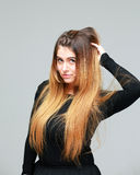 Portrait of beautiful young woman with long hair in a black dress Stock Image