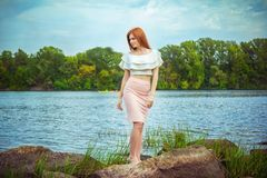 Portrait of beautiful young woman with long red hair, wearing elegant pink skirt and white top Stock Image