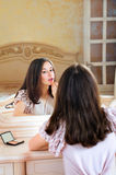 Portrait of beautiful young woman looking at the mirror stock photography