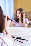 Portrait of beautiful young woman looking at the mirror royalty free stock photography