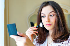Portrait of beautiful young woman looking at the mirror royalty free stock images