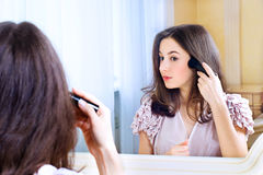 Portrait of beautiful young woman looking at the mirror royalty free stock image