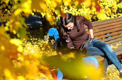 Portrait of a beautiful young woman looking to her dog while resting in the autumn park. Girl is sitting on brown wooden Royalty Free Stock Images