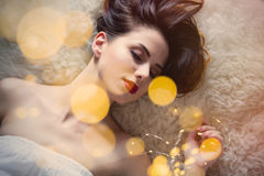 Portrait of beautiful young woman lying on fluffy blanket with c Royalty Free Stock Photos