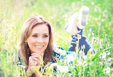 Portrait of a beautiful young woman lying in the grass Stock Photo