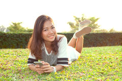 Portrait of beautiful young woman lying on green grass field and Royalty Free Stock Photo