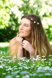Portrait of a beautiful young woman lying on green grass outdoors Stock Photo