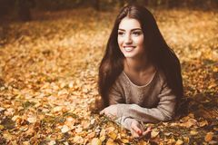 Lying on the ground. A portrait of a beautiful young woman lying on the ground with golden autumn leaves. Lifestyle, autumn fashion, beauty royalty free stock images