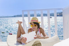 Portrait of beautiful young woman lying on a sunbed with tablet in the hand Stock Image