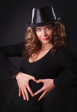 Portrait  of beautiful young woman making a heart shape. Beautiful young woman  in black hat and brown long ringlets hair making a heart shape Stock Image