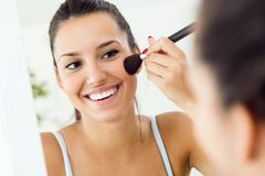 Beautiful young woman making make-up near mirror at home. Stock Images