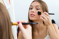 Beautiful young woman making make-up near mirror at home. Royalty Free Stock Images