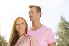 Portrait of beautiful young woman with man in park Stock Photo