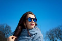 Portrait of beautiful young woman with mirrored sunglasses outdoors over blue sky during early spring time. royalty free stock images