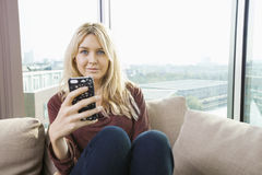 Portrait of beautiful young woman with mobile phone at home Royalty Free Stock Photo
