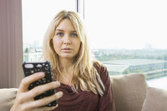 Portrait of beautiful young woman with mobile phone at home Stock Photos