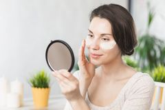 Portrait Of Beautiful Young Woman with Natural Makeup applying white Under Eye Patches Beauty Mask On Face. Girl with stock image