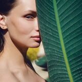Portrait of a Beautiful young woman with natural makeup holds a big green leaf