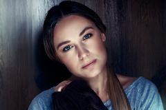 Genuine women`s beauty. Portrait of a beautiful young woman with natural makeup over wooden background, calm and peaceful female, genuine women`s beauty concept Royalty Free Stock Image