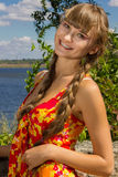 Portrait of a beautiful young woman in nature. With long brown hair braided in a long bright dress and bright makeup Stock Photography