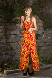 Portrait of a beautiful young woman in nature. With long brown hair braided in a long bright dress and bright makeup Royalty Free Stock Image