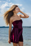 Portrait of a beautiful young woman in nature. With long brown hair in a short dress Stock Photography