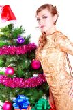 Portrait of a beautiful young woman near the Christmas tree and. Presents isolated over white background Royalty Free Stock Photos