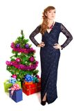Portrait of a beautiful young woman near the Christmas tree and. Presents isolated over white background Royalty Free Stock Images