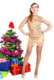 Portrait of a beautiful young woman near the Christmas tree and. Presents isolated over white background Stock Photo