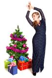 Portrait of a beautiful young woman near the Christmas tree and. Presents isolated over white background Royalty Free Stock Image