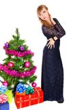 Portrait of a beautiful young woman near the Christmas tree and Royalty Free Stock Image