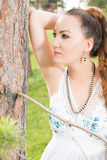 Portrait of  beautiful young woman near tree. Portrait of beautiful young woman near tree in summer park Stock Image