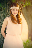 Portrait of beautiful young woman near tree on the wonderful par. K background Stock Photo
